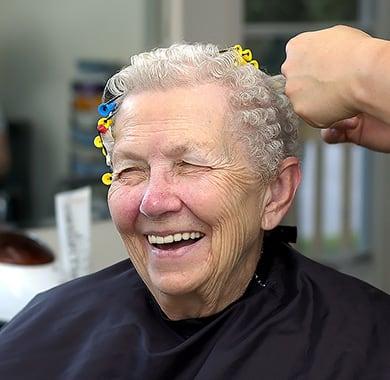 Ältere Dame lächelt während ihr bei 100% Dein Friseurteam die Locken gewickelt werden